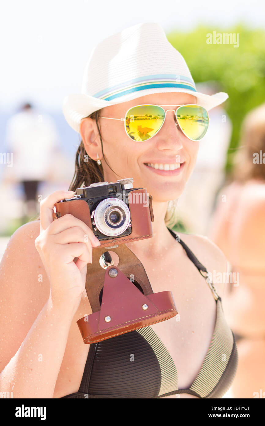 Young happy woman in black bikini having fun with old photo camera at the summer beach holidays. - Stock Image