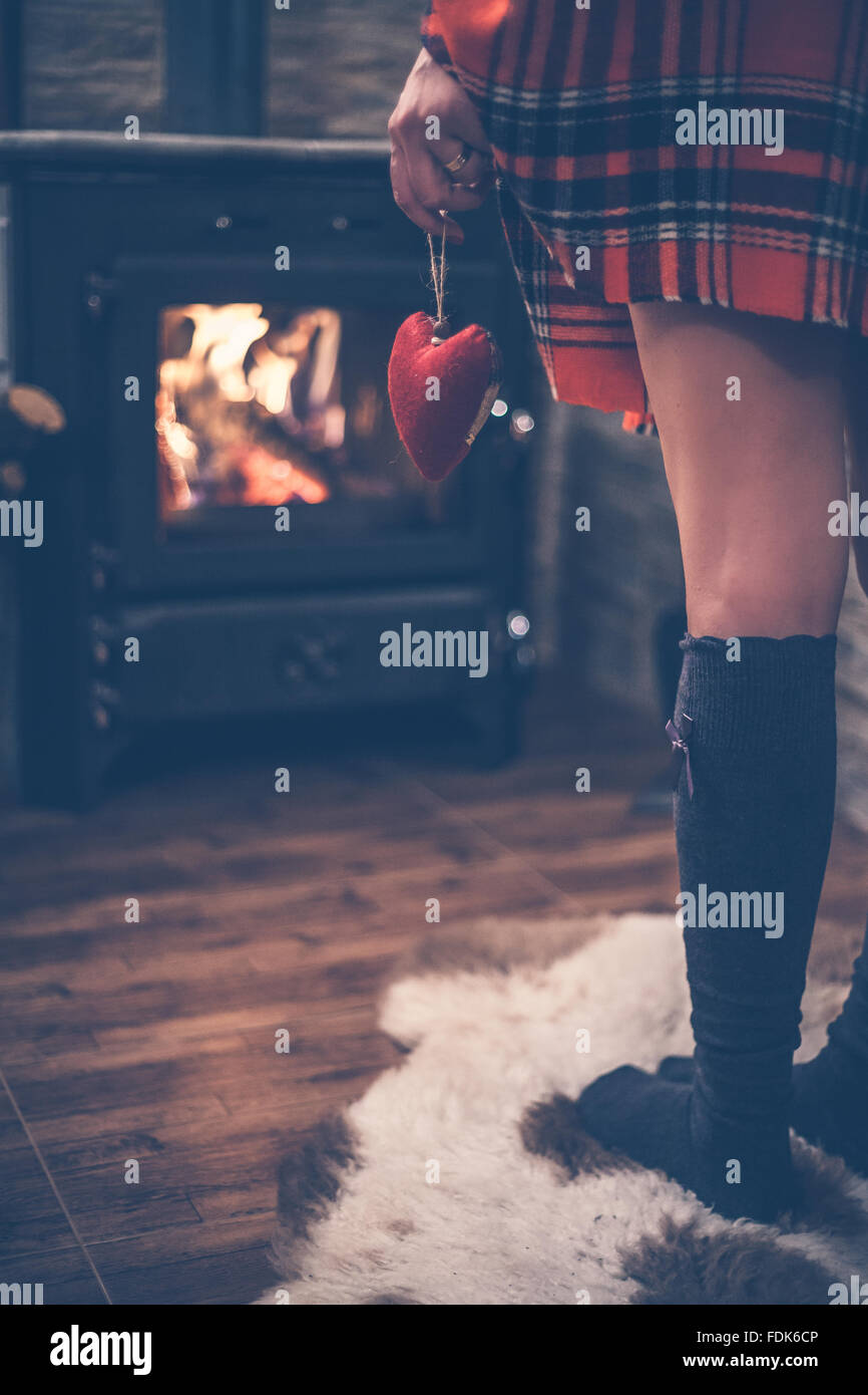 Rear view of a woman standing in front of wood burning stove holding red heart in her hand - Stock Image