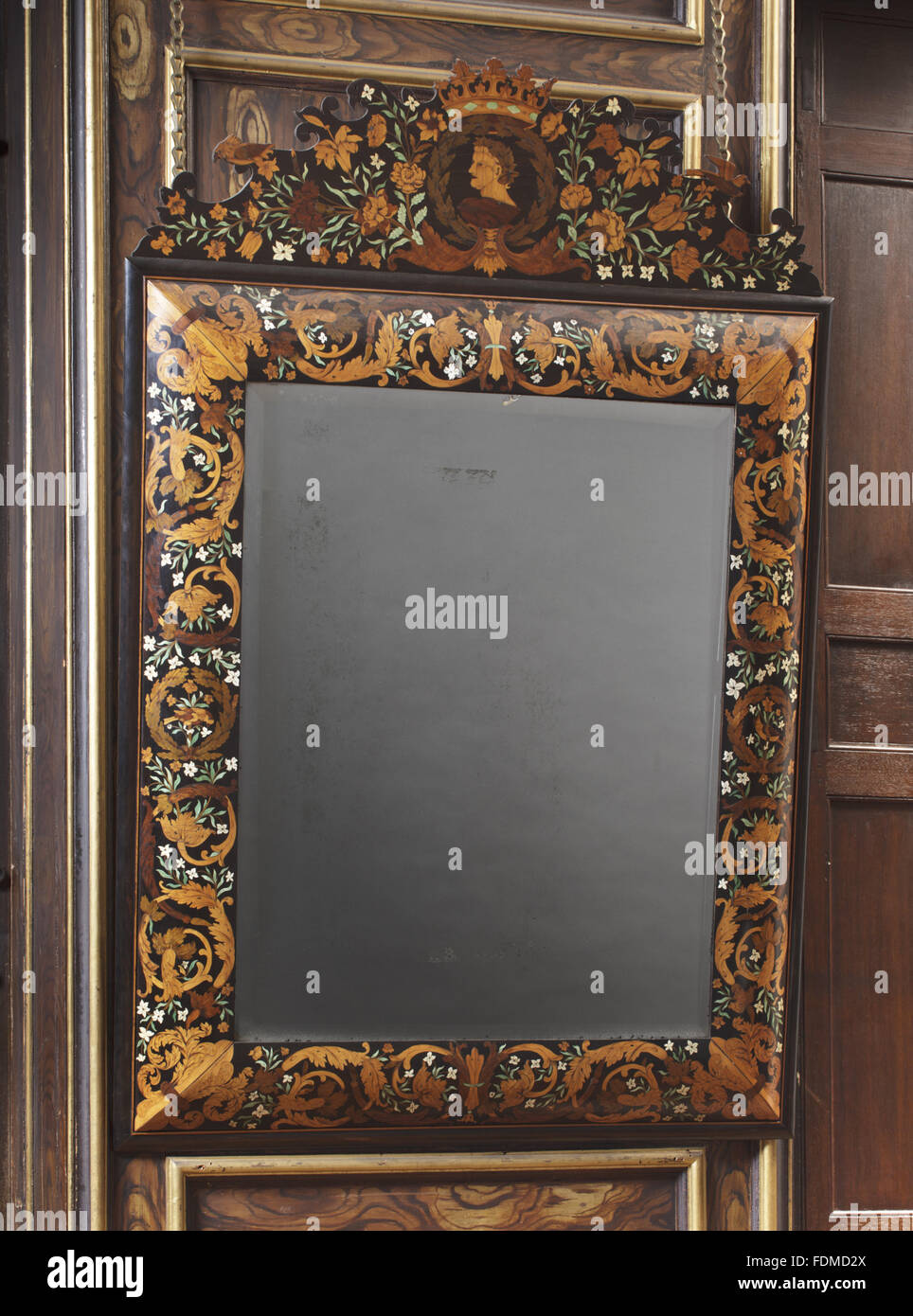 Wall mirror, 1675, of ebony, decorated with floral marquetry in various woods and ivory, some of which is stained - Stock Image