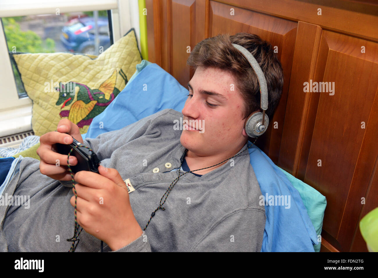 teenage boy lies on his bed while using the internet on his mobile