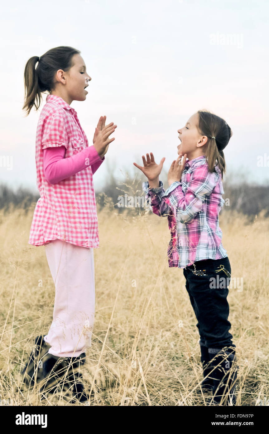 Girls in field playing hand clapping games - Stock Image