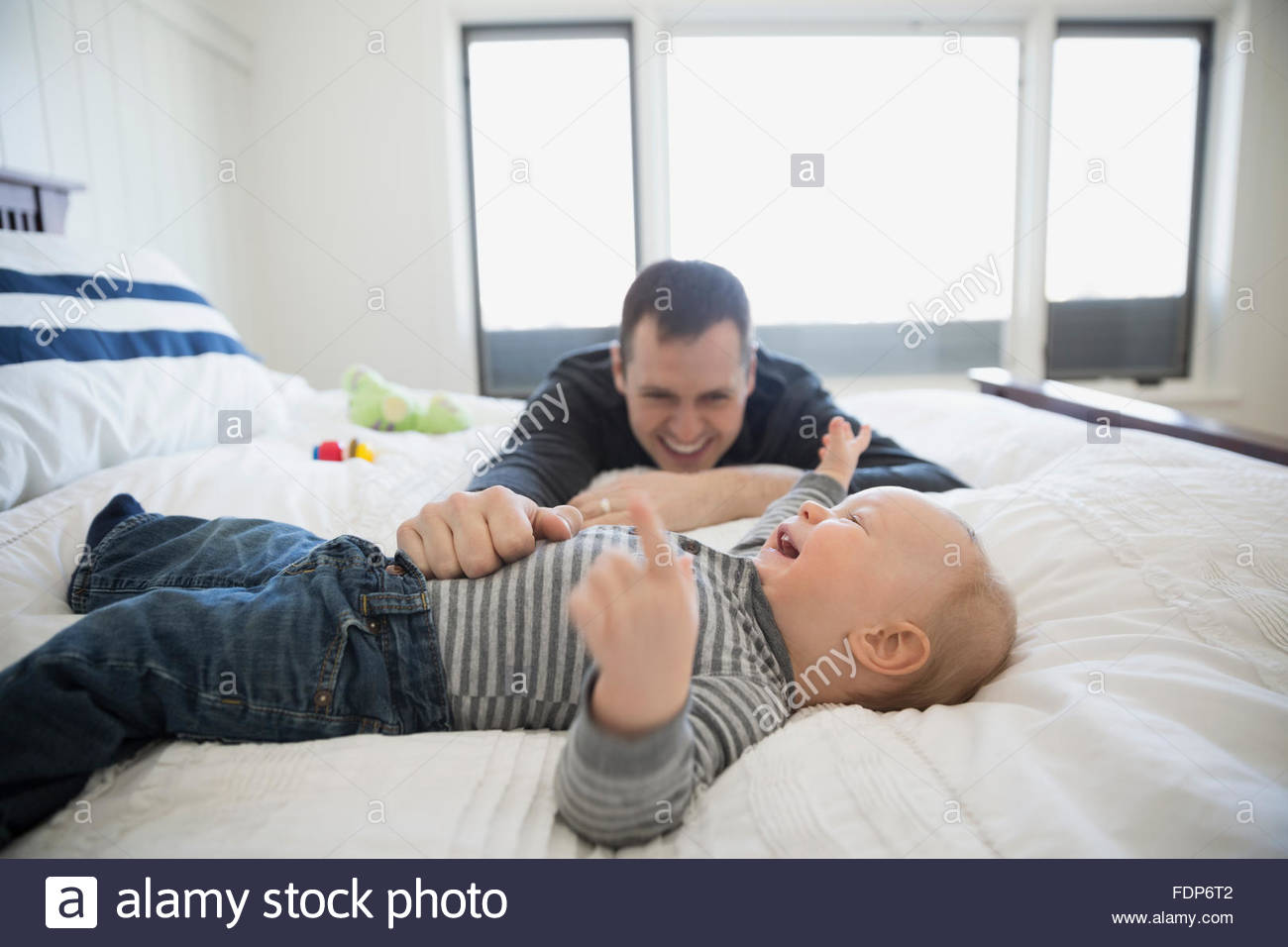 Father and baby son laughing on bed - Stock Image
