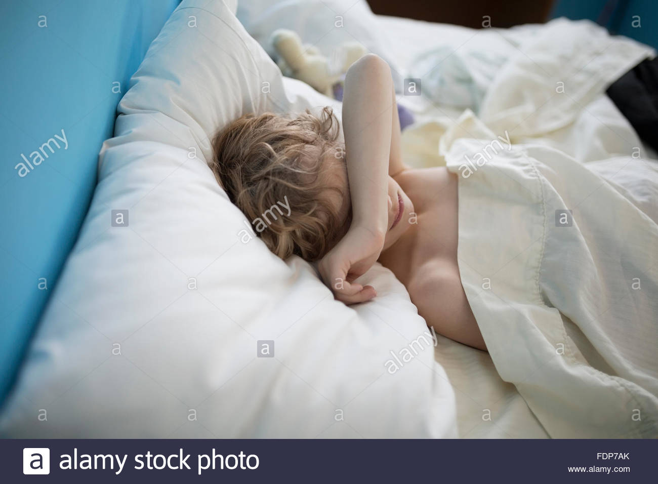 Tired boy sleeping with arm over eyes - Stock Image