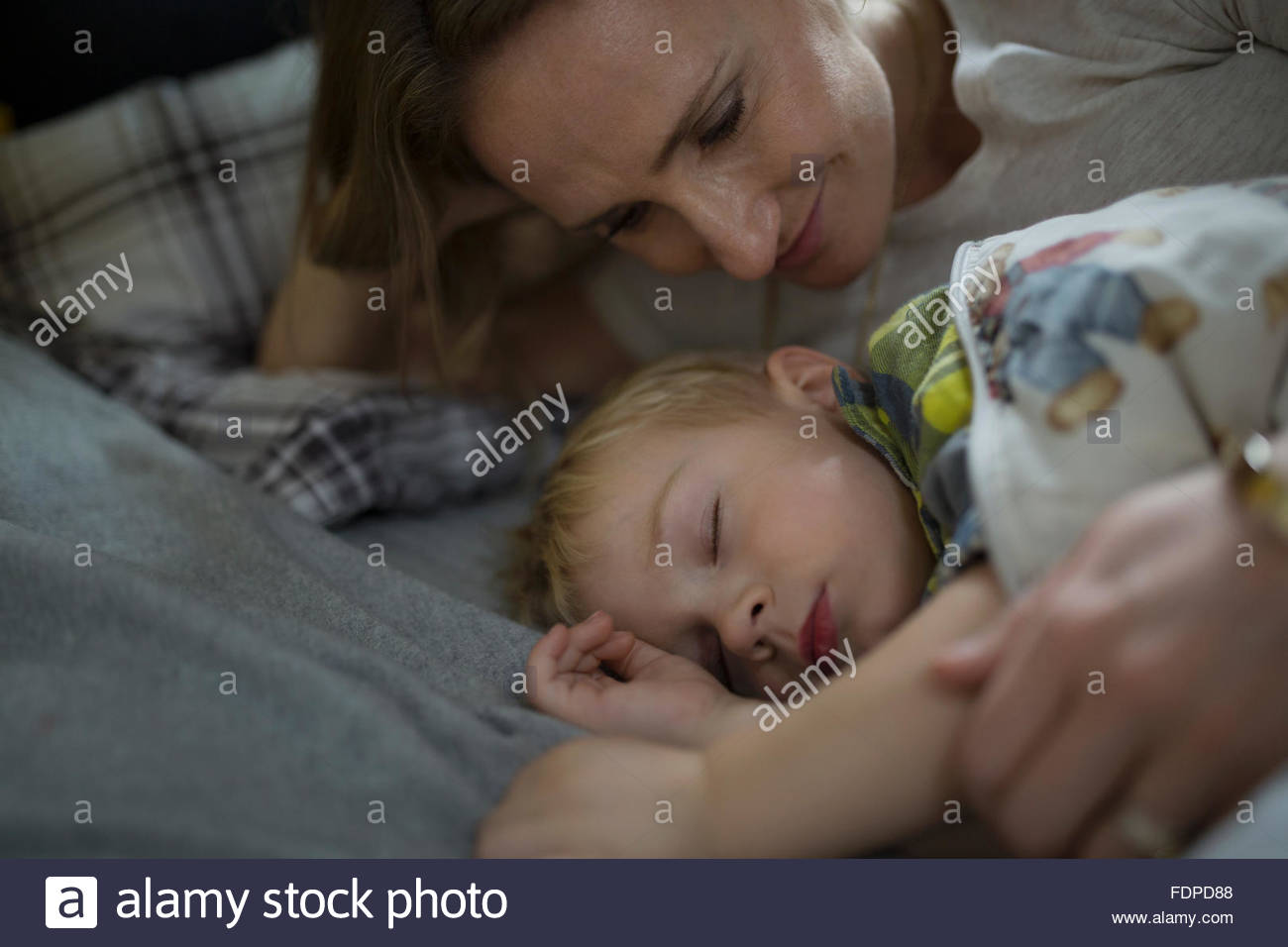 Affectionate mother watching sleeping son in bed - Stock Image