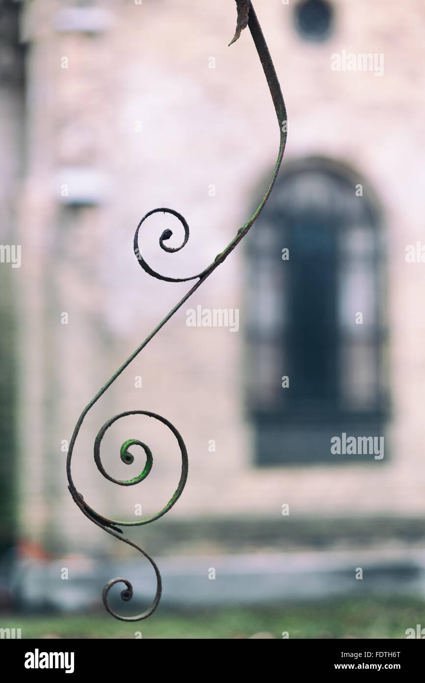 Elegant and stylish vintage metal ornament spiral in the autumn park on the background of the walls and windows - Stock Image