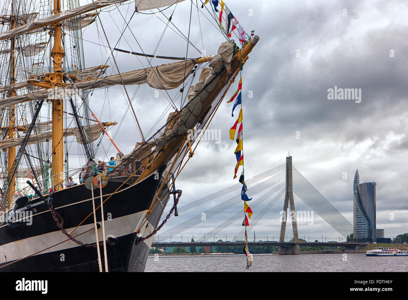 Big sailboat on the waterfront of the capital of Latvia in Riga on the background of a suspension bridge and clouds - Stock Image