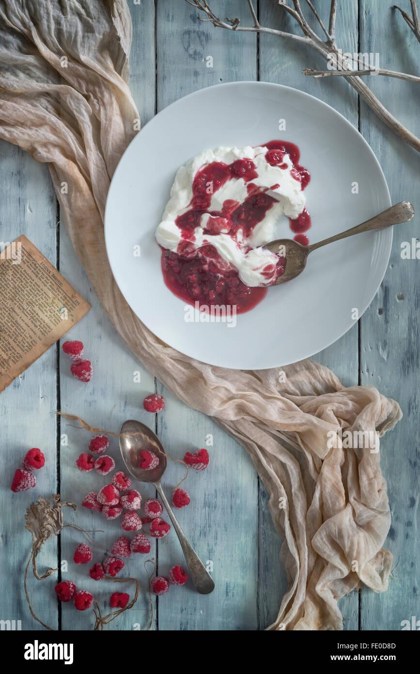 Raspberries and raspberry coulis with organic yogurt. - Stock Image