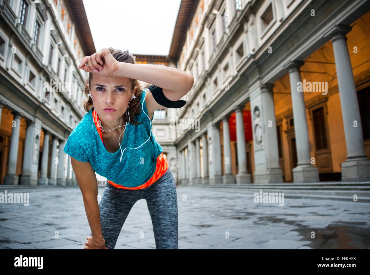 Now it is time to invest in your body and no matter you are at hometown or traveling. Young fitness female is catching - Stock Image