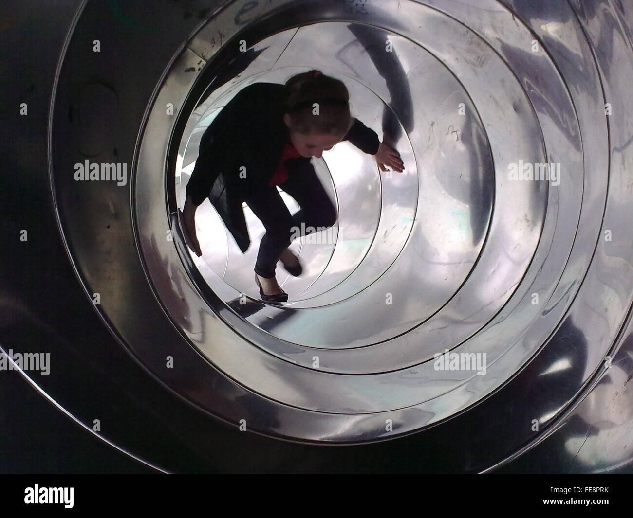 Teenage Girl Walking Inside Tunnel Slide - Stock Image