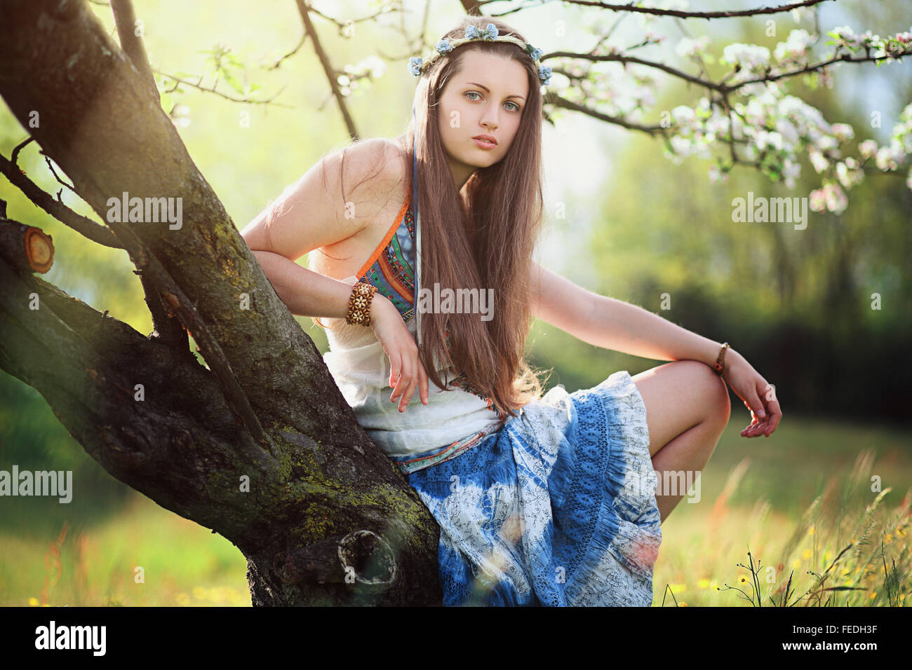 Romantic woman in flower meadow . Hippie and gypsy dress - Stock Image