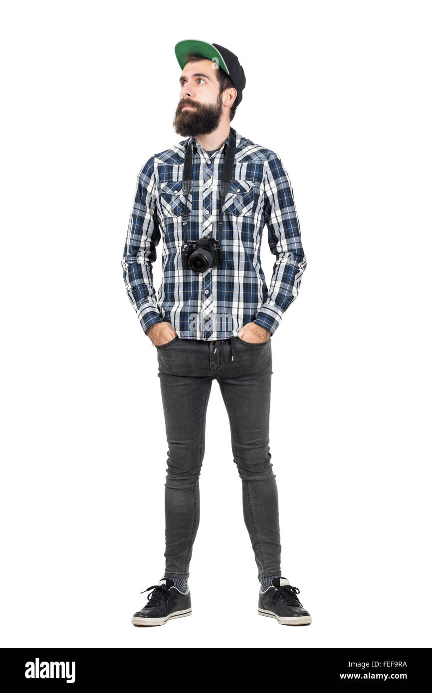 Relaxed hipster wearing black dslr camera over neck with hands in pockets. Full body length portrait isolated over - Stock Image