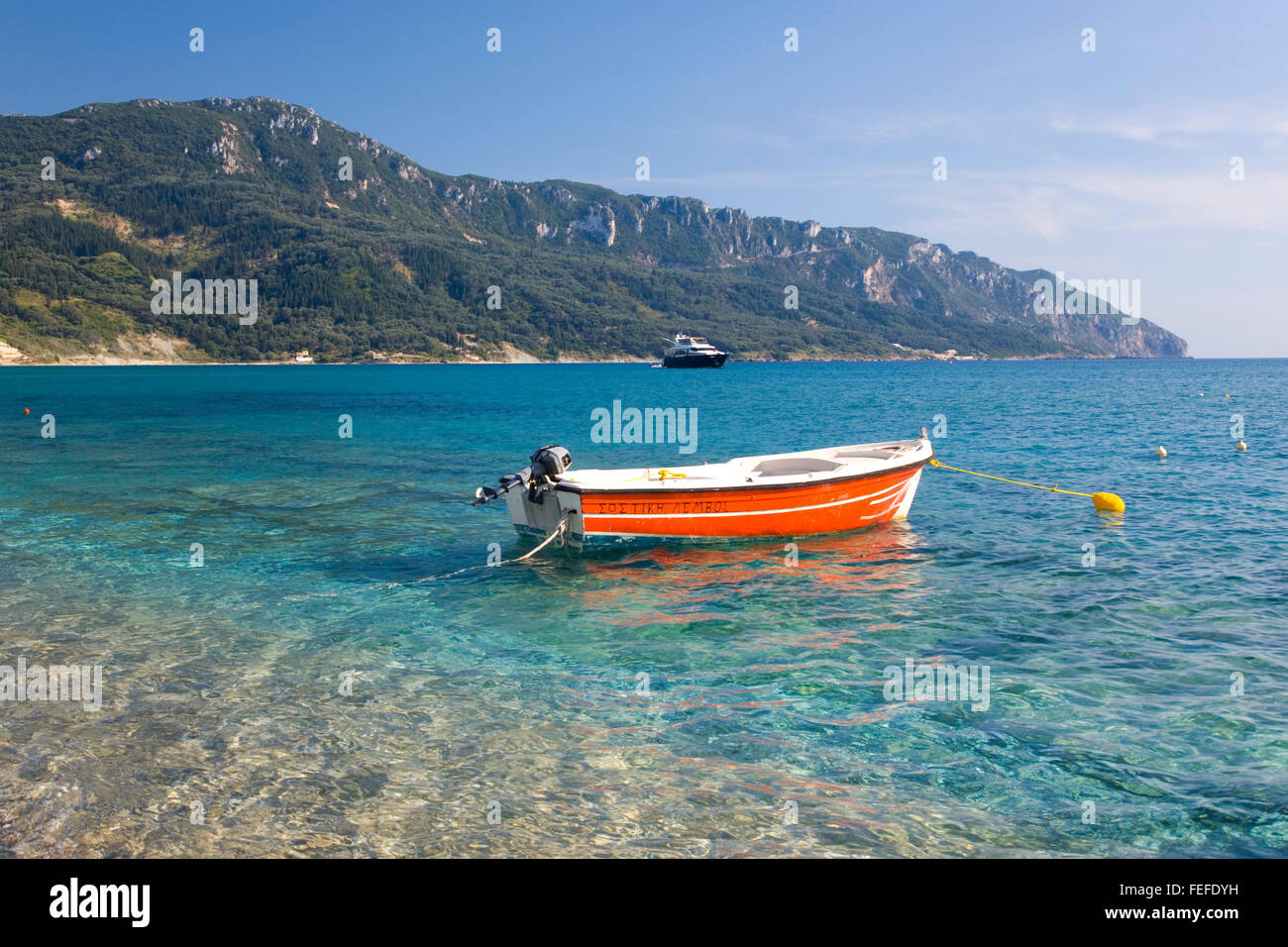 Agios Georgios, Corfu, Ionian Islands, Greece. Colourful boat moored in clear turquoise water, Cape Taxiarhis beyond. - Stock Image