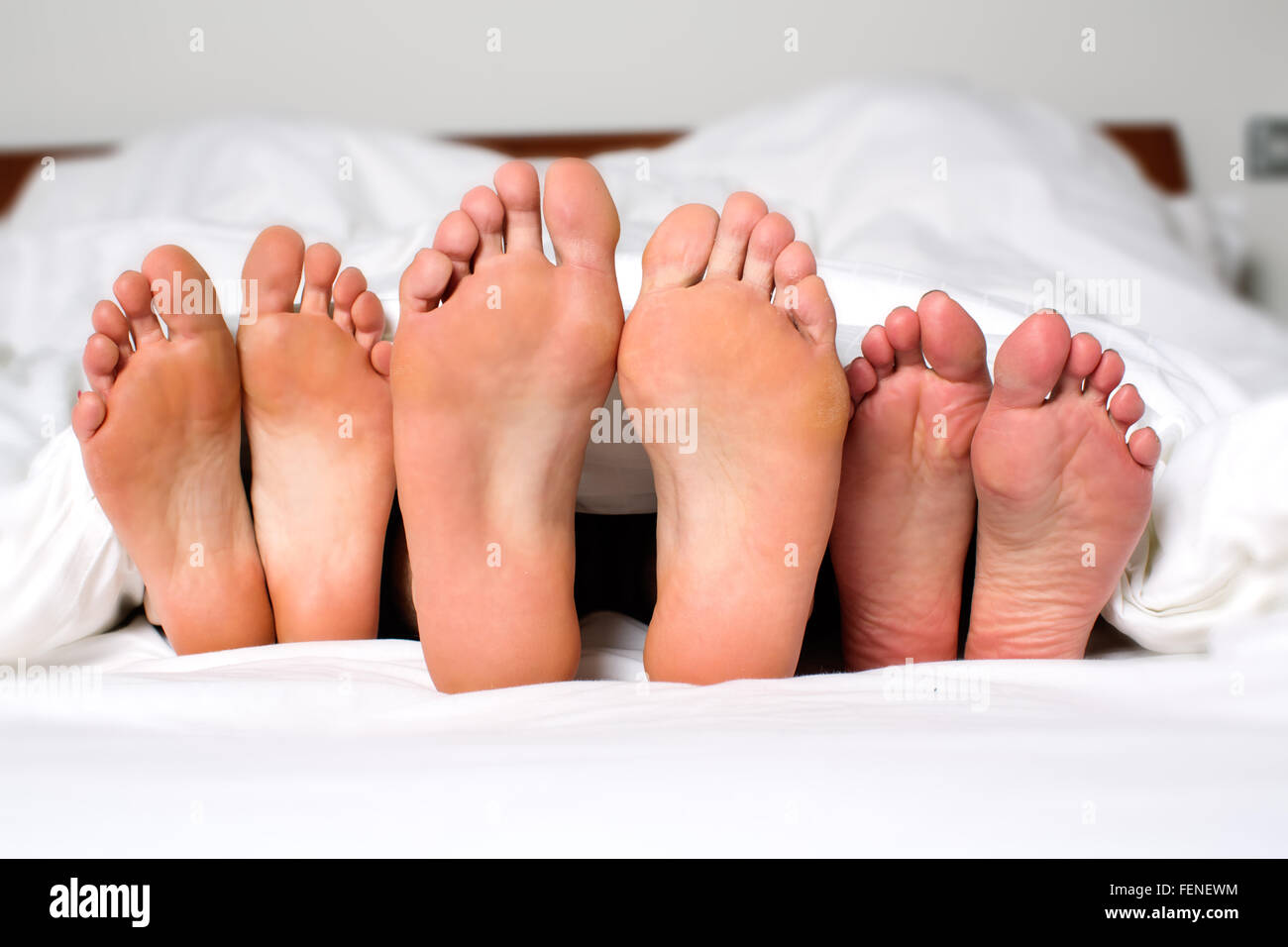 Close-Up Of Bare Feet In Bed Stock Photo
