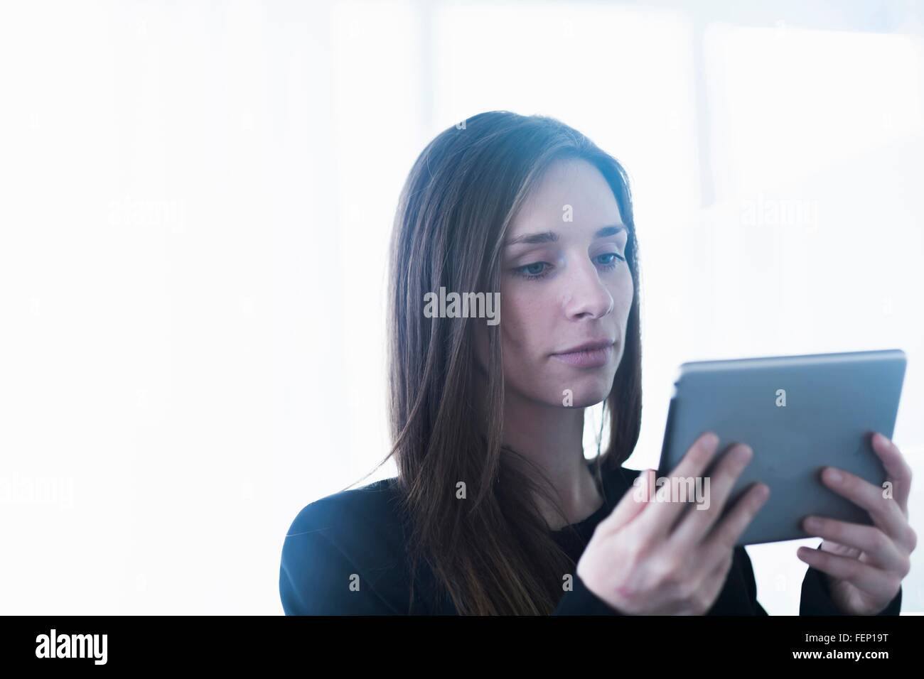 Head and shoulders of young woman using digital tablet - Stock Image