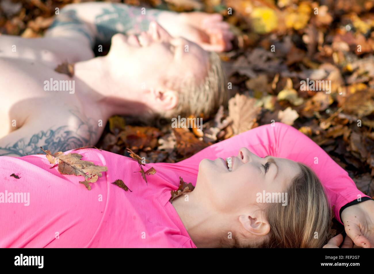 Side view of couples head and shoulders lying on autumn leaves looking up smiling - Stock Image