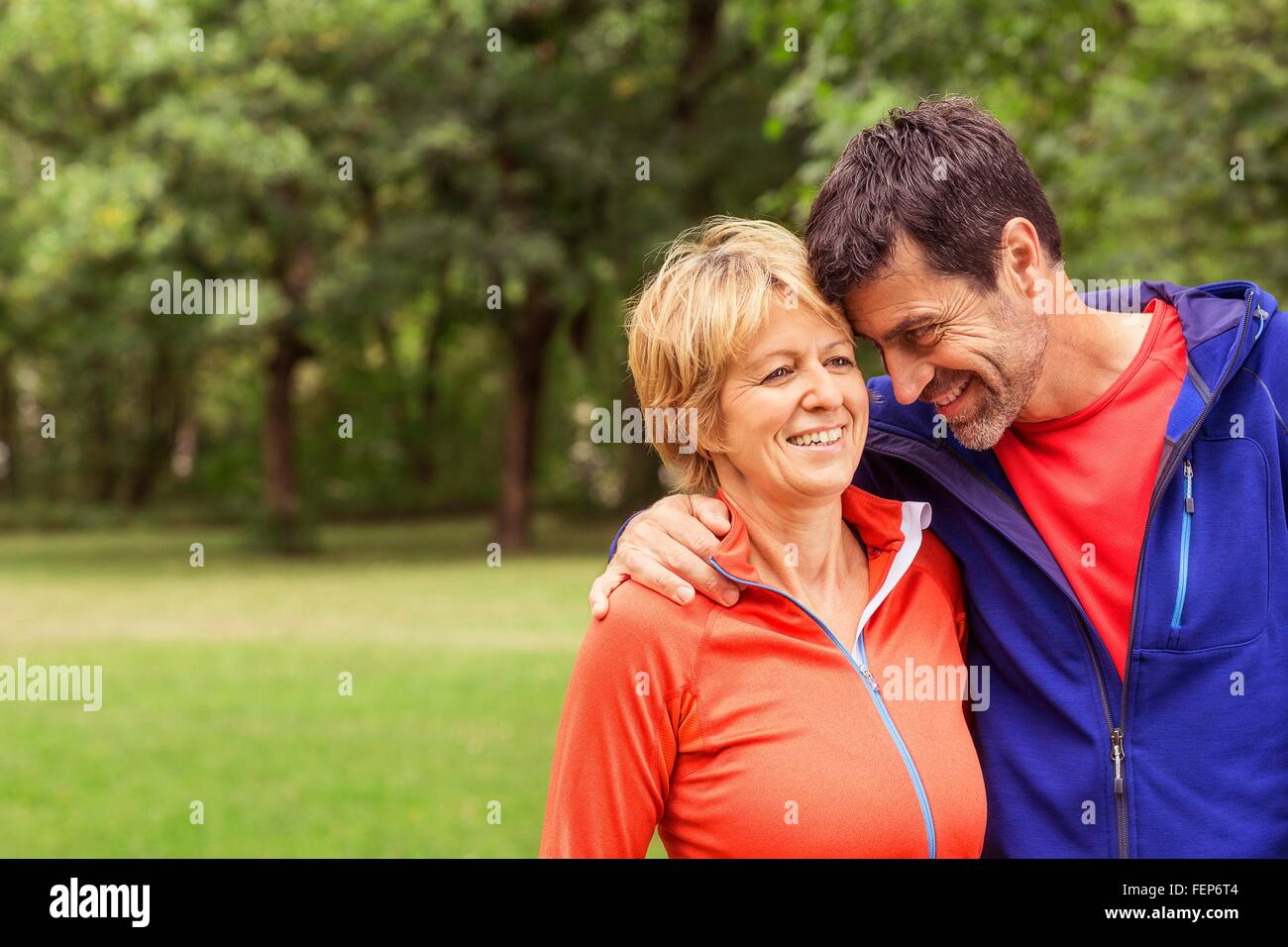 Couple wearing sports clothing, outdoors, hugging, smiling - Stock Image