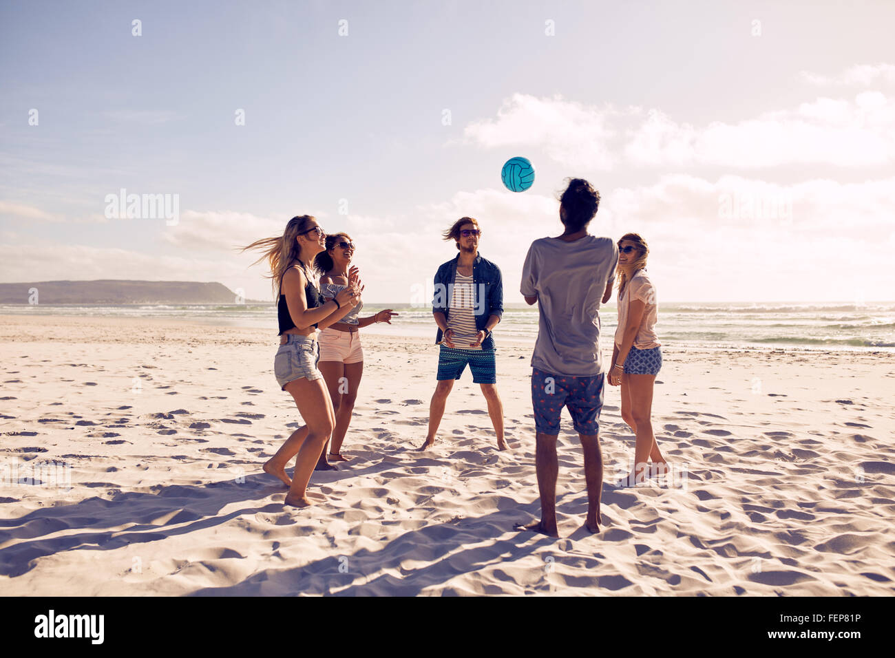 Group of young people playing with ball at the beach. Young friends enjoying summer holidays on a sandy beach. - Stock Image