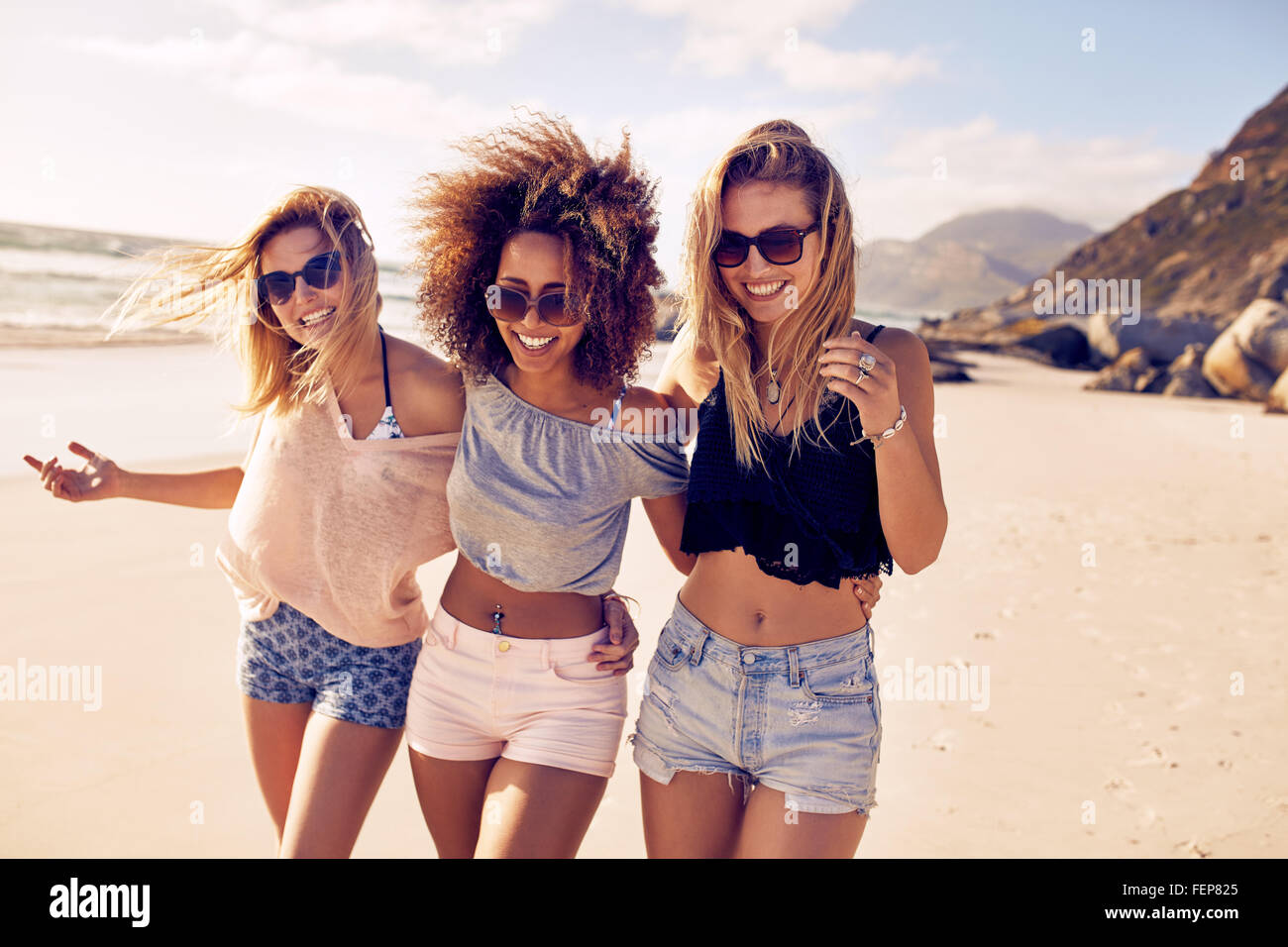 Portrait of three young female friends walking on the sea shore looking at camera laughing. Multiracial young women - Stock Image