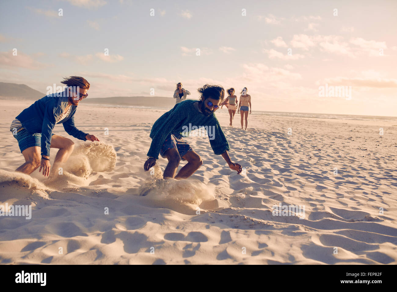 Young men running race on the beach. Group of young people playing games on sandy beach on a summer day. - Stock Image