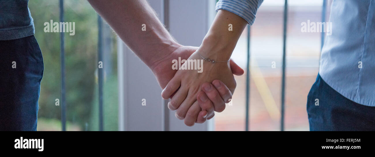 Two People With Hands Together Using A Bracelet With Infinity Symbol