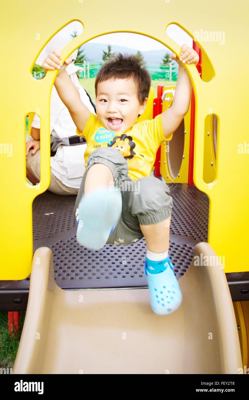 Portrait Of Cheerful Boy On Playground Slide - Stock Image