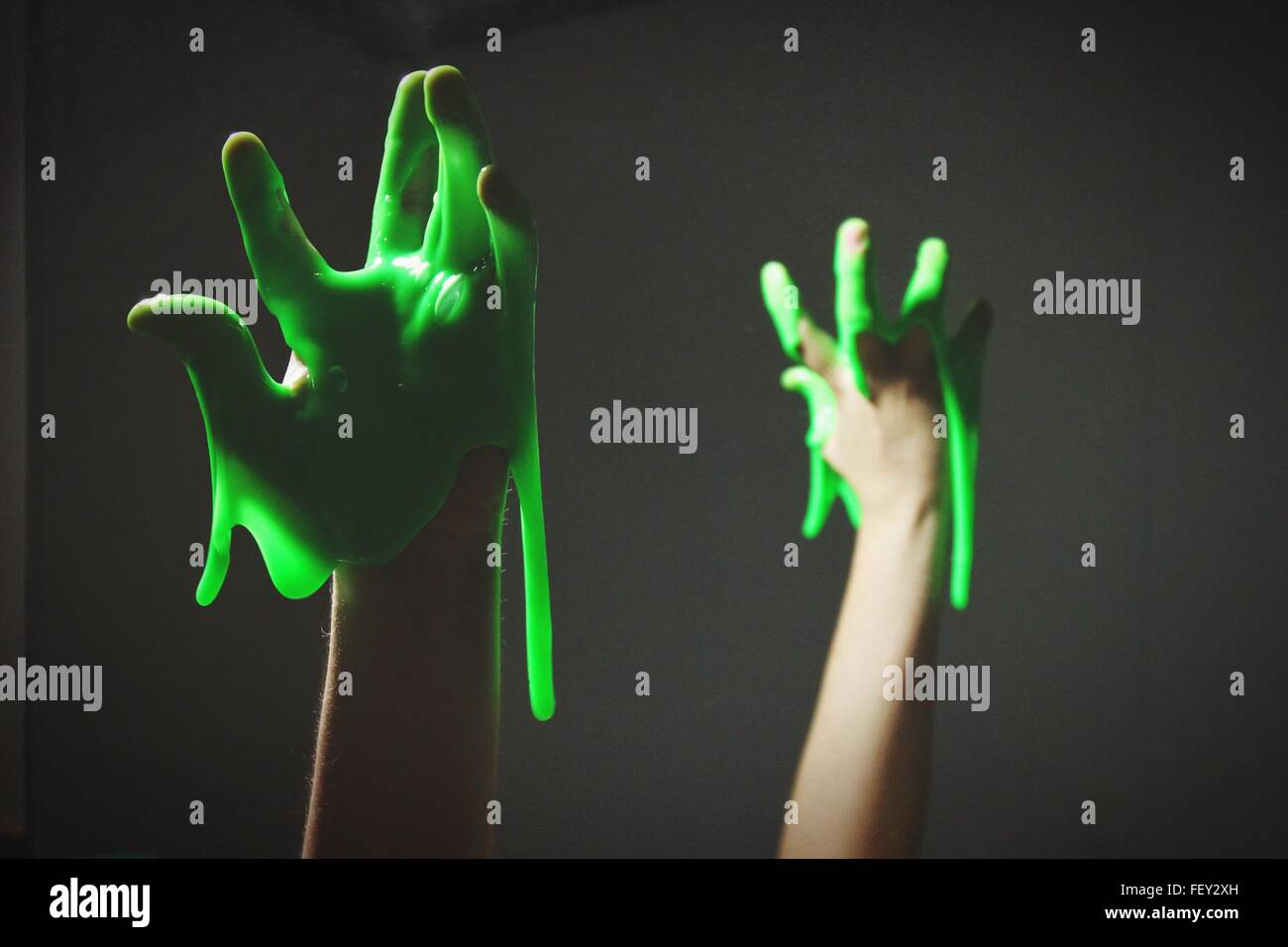 Cropped Hand With Green Slime Against Black Background - Stock Image