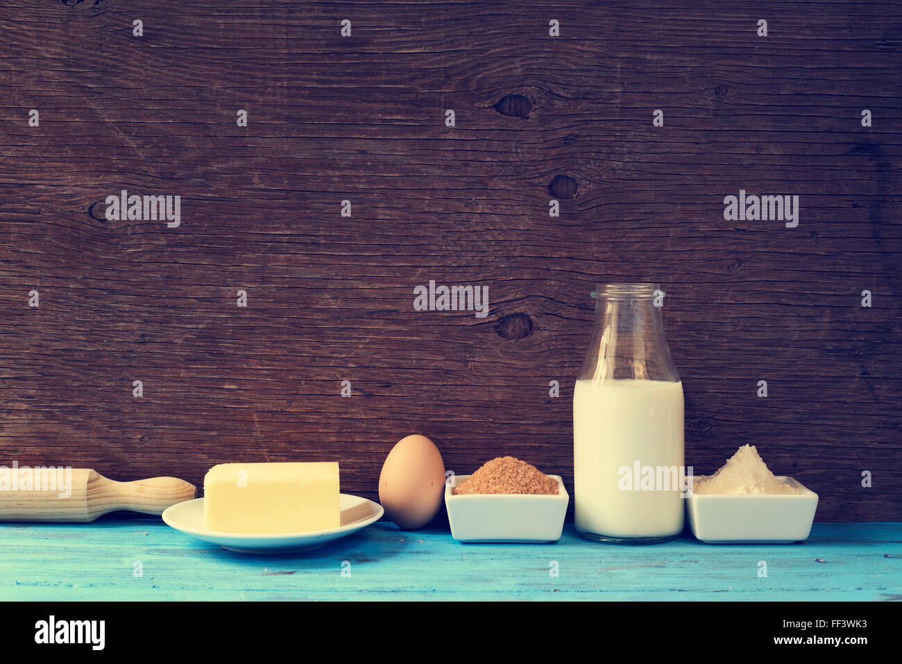 some ingredients for preparing cookies or a cake, such as milk, eggs, flour, butter and brown sugar on a blue rustic - Stock Image