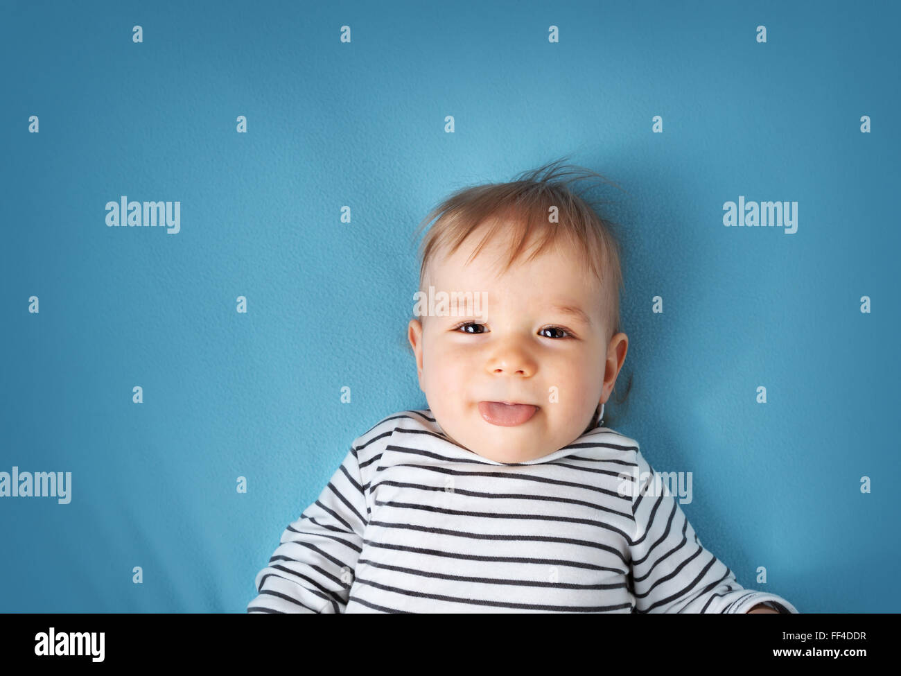little boy on blue blanket background - Stock Image