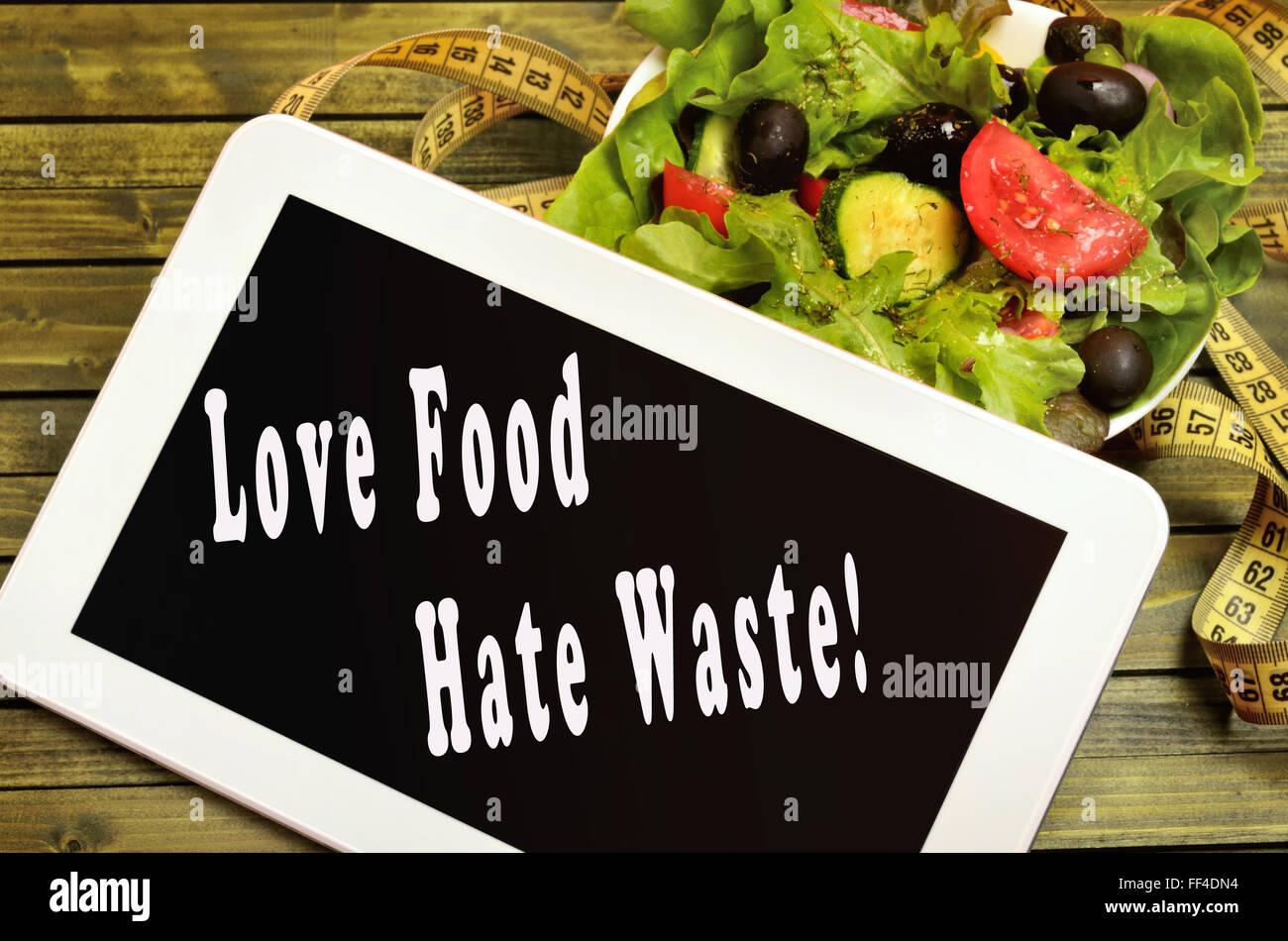 Love food Hate waste written on digital tablet - Stock Image