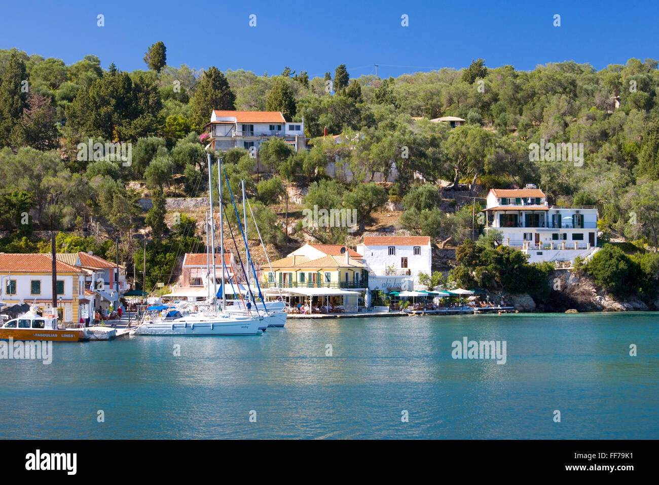 Lakka, Paxos, Ionian Islands, Greece. View to the village across the clear turquoise waters of Lakka Bay. - Stock Image