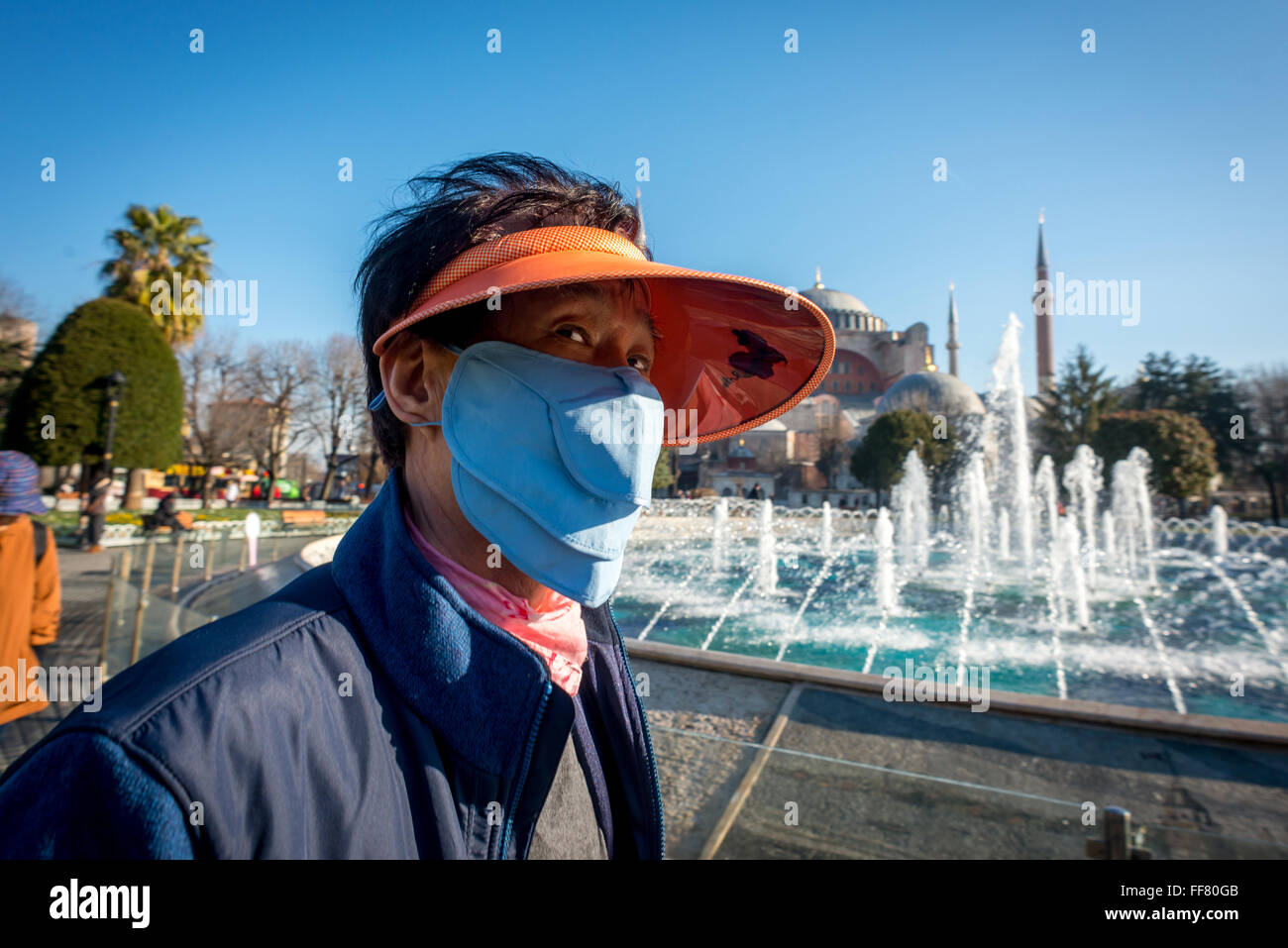 A Japanese tourist wearing a face-mask near the Sultan Ahmed Mosque in Istanbul, Turkey. - Stock Image
