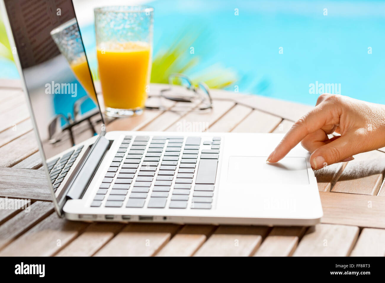 in garden a woman surfing internet on laptop blur pool background