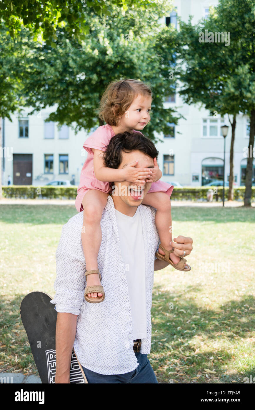 Daughter covering father's eyes - Stock Image
