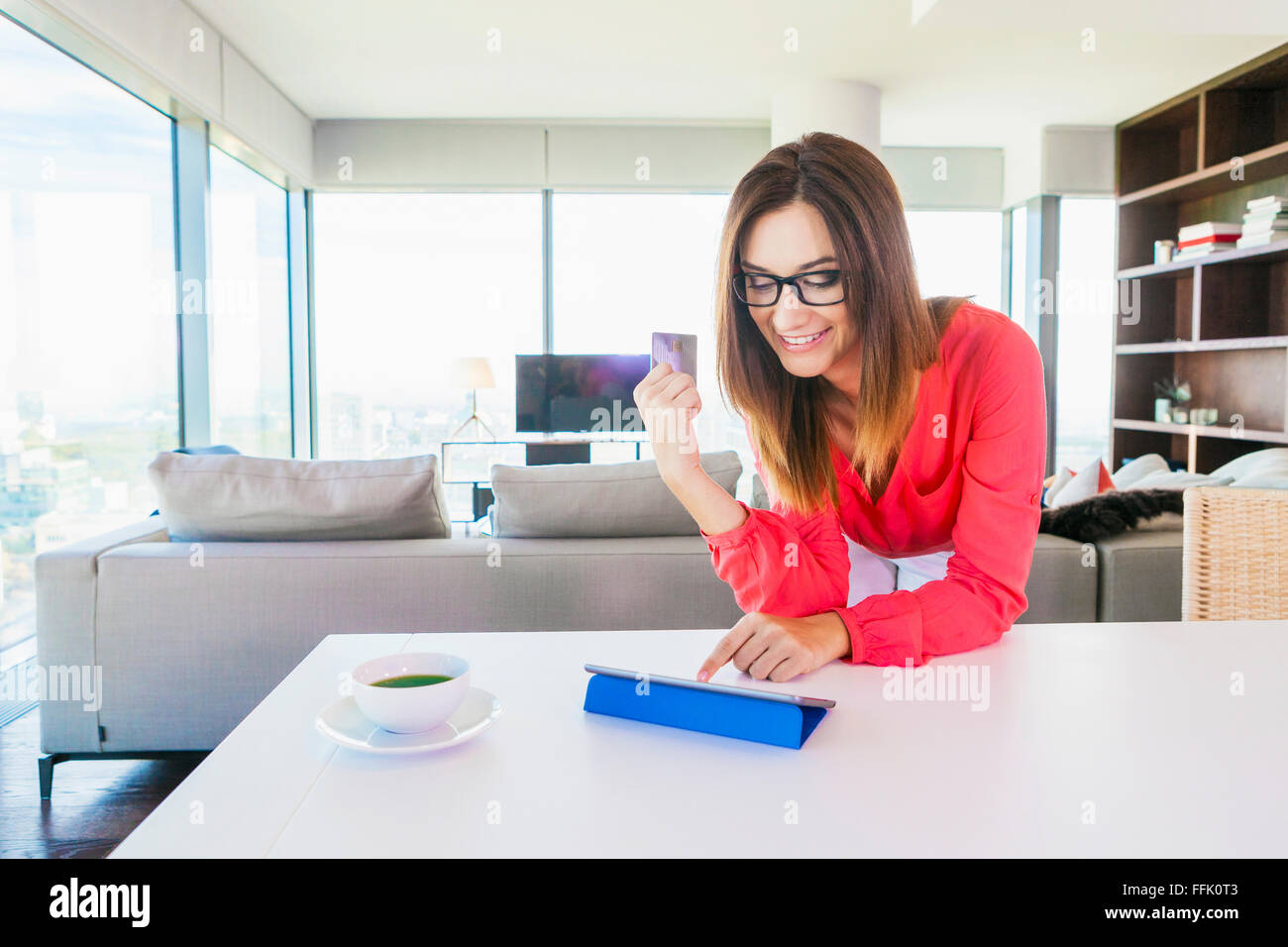 Woman in apartment shopping online with digital tablet - Stock Image