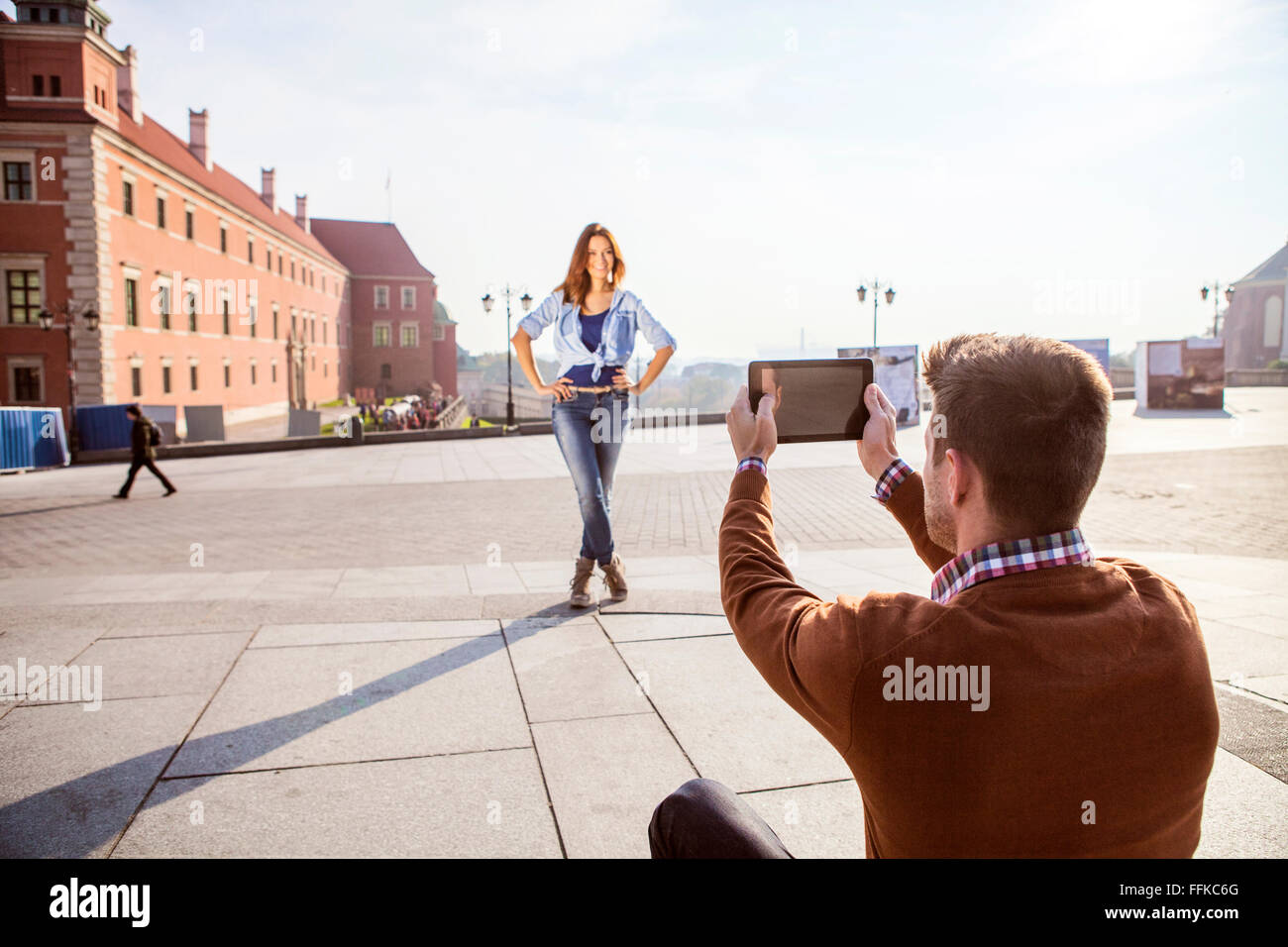 Mid adult man taking a picture of girlfriend - Stock Image