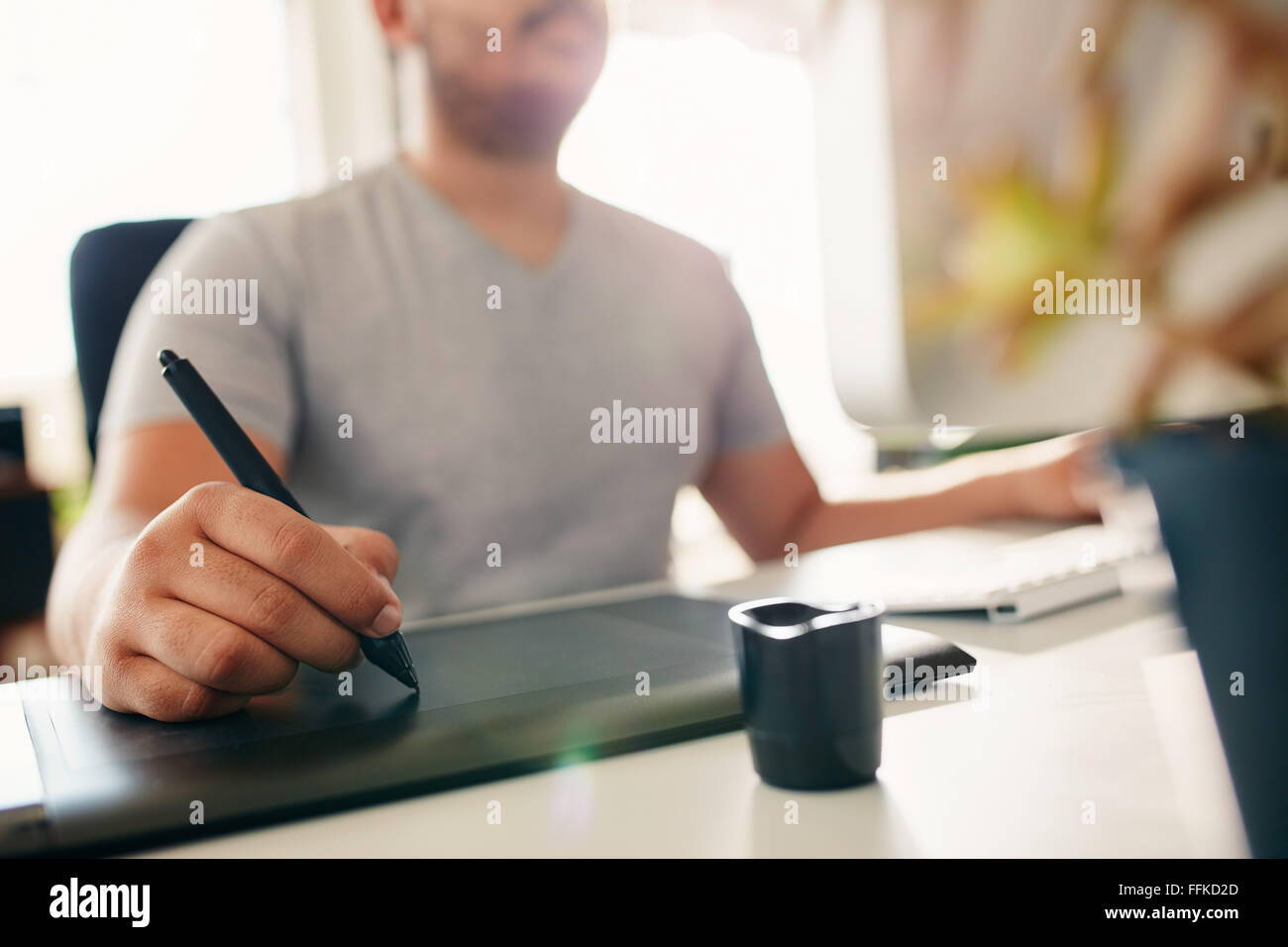 Hand of male designer working at his desk using stylus and digital graphics tablet. - Stock Image