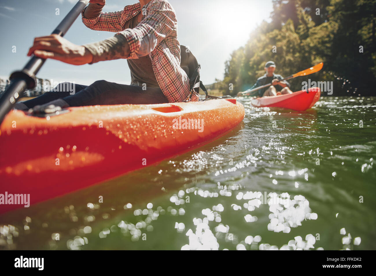Cropped image of woman kayaking with a man in background. Couple canoeing in a lake on a summer day. - Stock Image