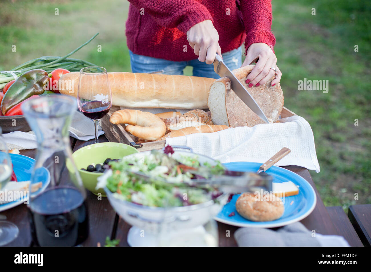 Person on garden party slicing loaf of bread - Stock Image