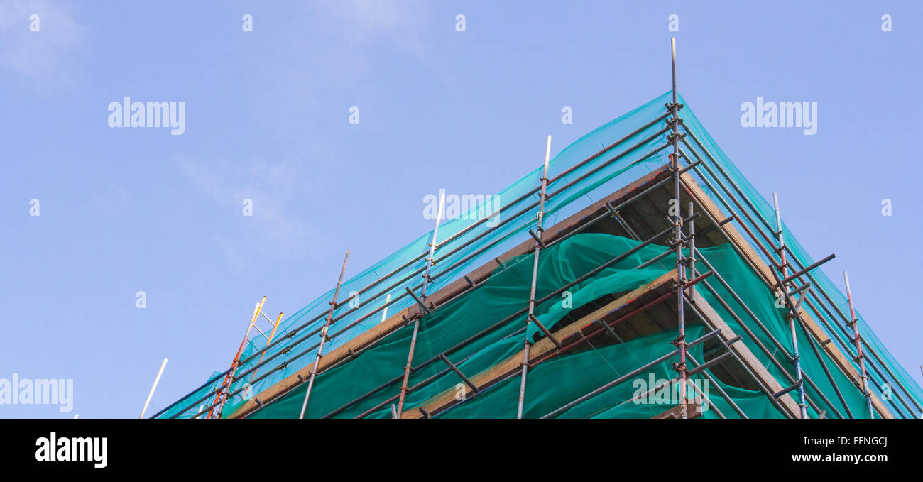 A tall building surrounded by scaffolding during construction work and under a blue sky. - Stock Image