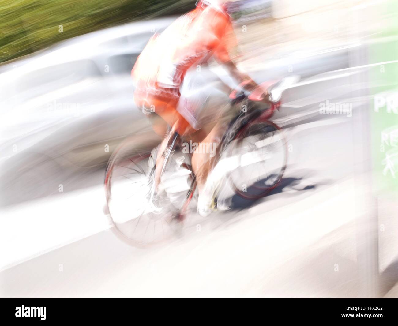 Blurred Motion Of Man Riding Bicycle On Road During Sunny Day - Stock Image