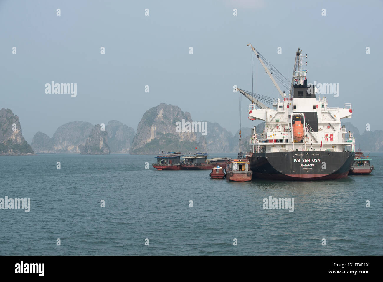 A supply ship from Singapore loading or unloading cargo from communities around Halong Bay, Vietnam - Stock Image