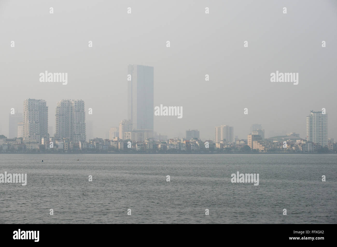 Mist, fog or smog pollution in a hazy skyline of Hanoi viewed over Westlake, Vietnam, January - Stock Image