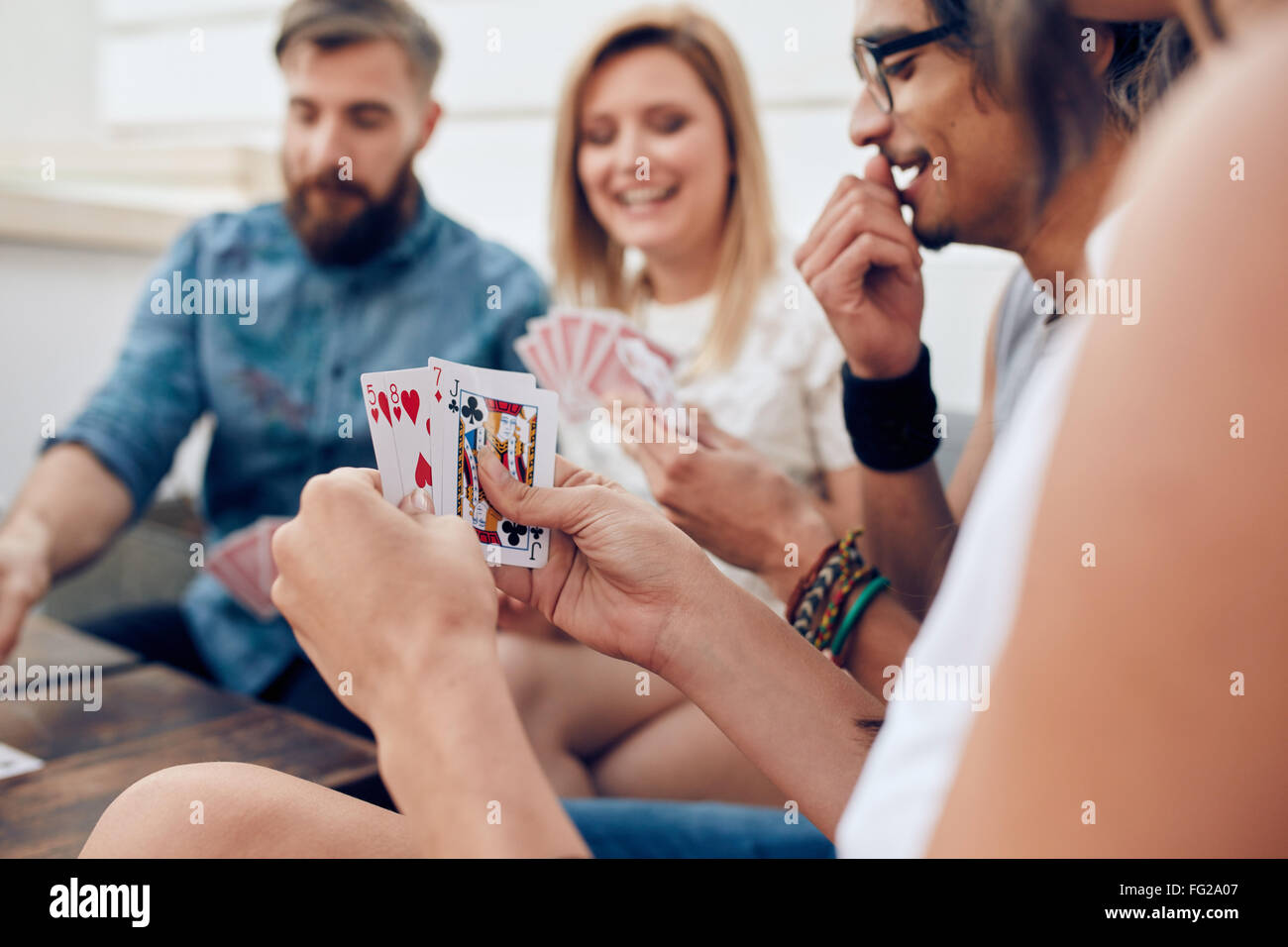 Group of friends sitting together playing cards. Focus on playing cards in hands of a woman during a party. - Stock Image