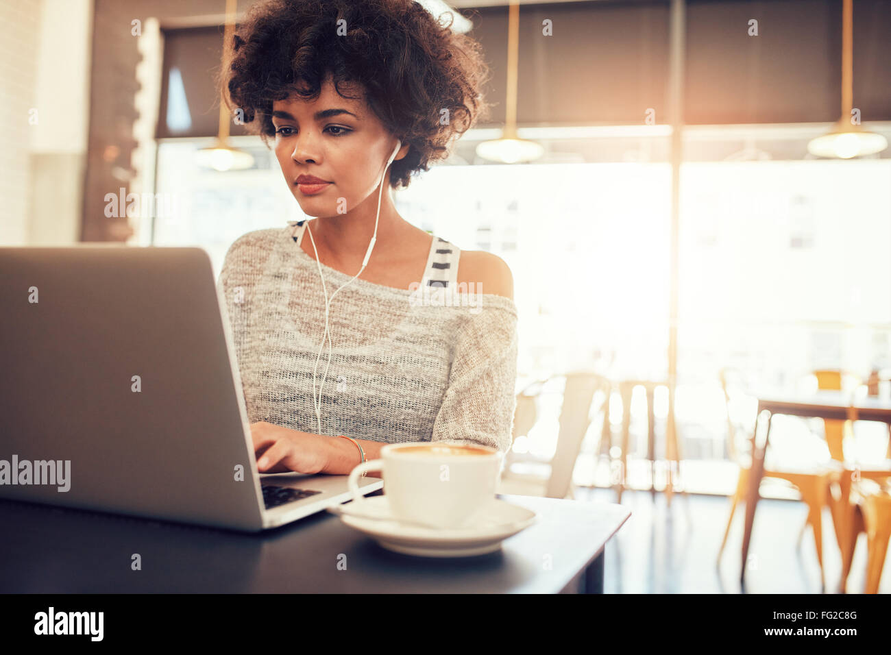 Portrait of beautiful young woman with earphones working on laptop while sitting at a coffee shop. African female - Stock Image