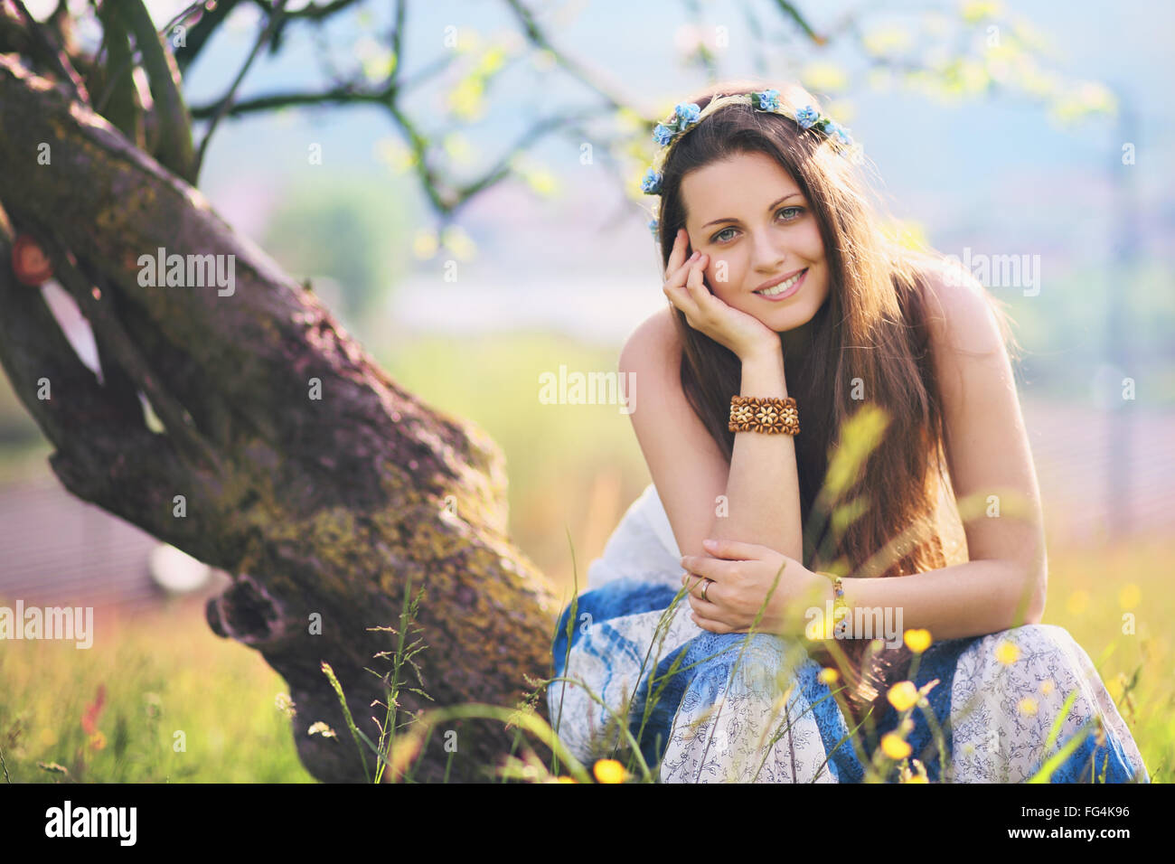 Smiling and joyful woman in spring meadow. Nature and harmony - Stock Image
