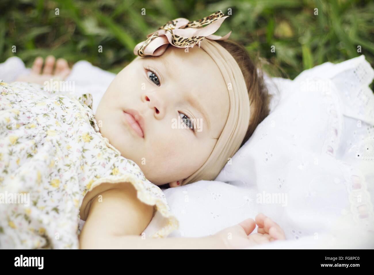 Portrait Of Baby Girl Lying Outdoors - Stock Image