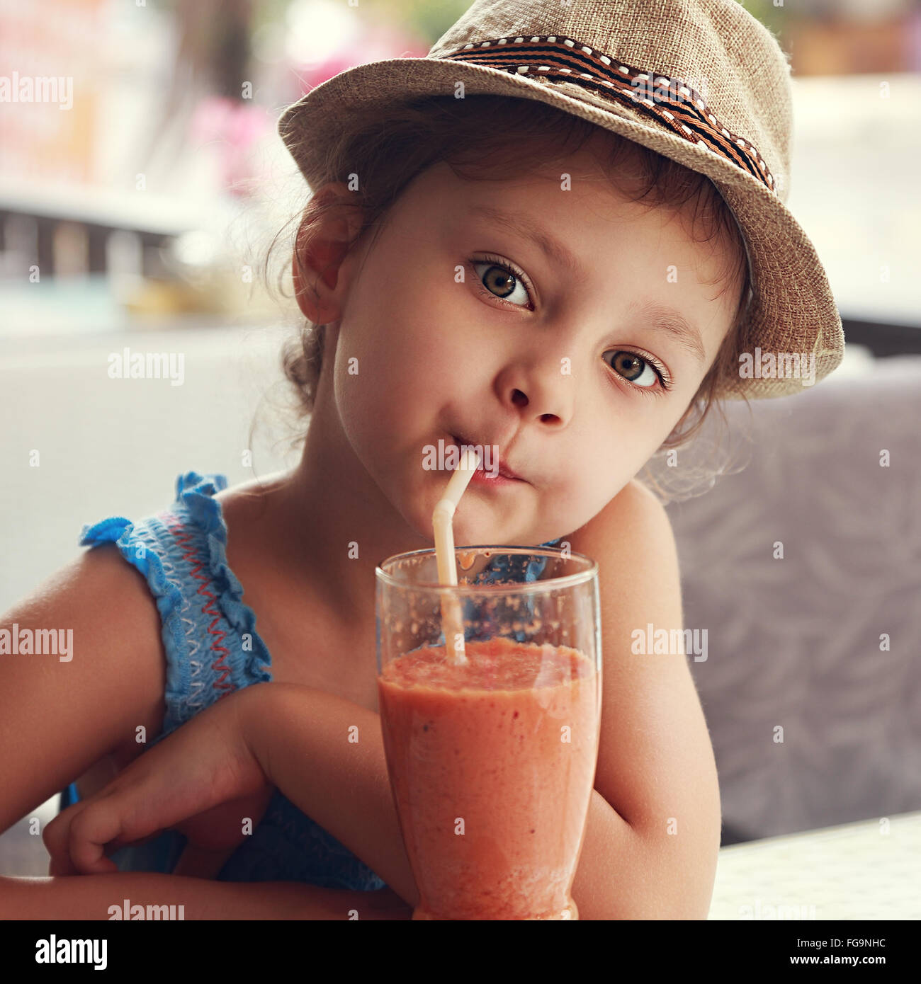 Fun cute kid girl drinking healthy smoothie juice in street restaurant. Closeup toned portrait - Stock Image
