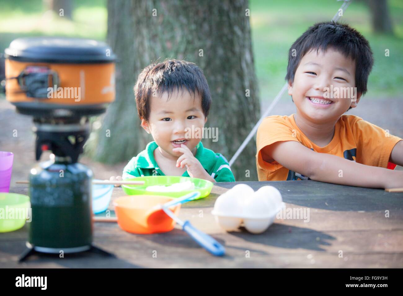 Portrait Of Siblings Playing With Toys During Camping - Stock Image