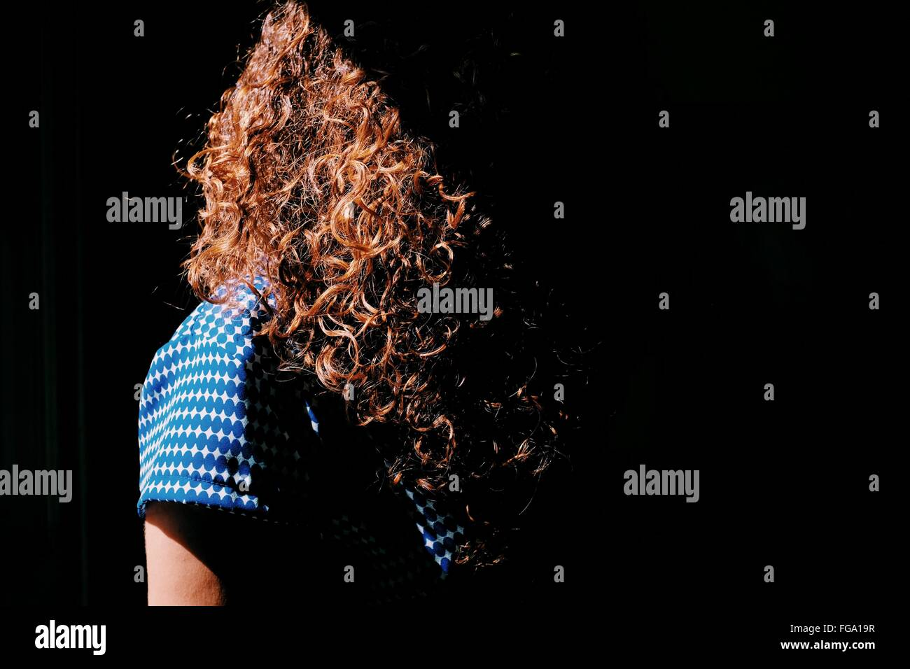 Woman With Curly Brown Hair In Sunlight - Stock Image