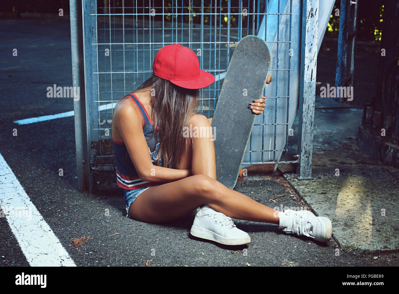 Skater girl seated on the street . Urban shot - Stock Image
